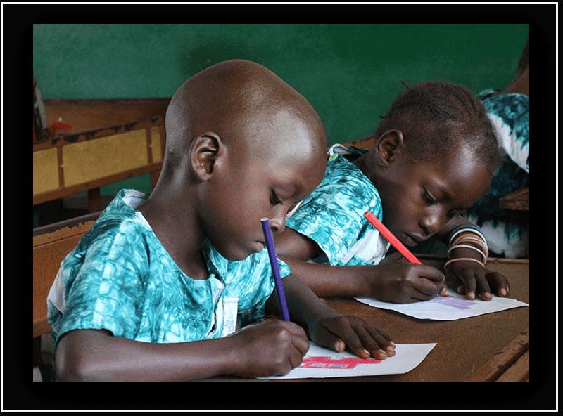 to Gambiske barn sitter foran en pult på skolen og tegner. Innredningen er meget enkel.