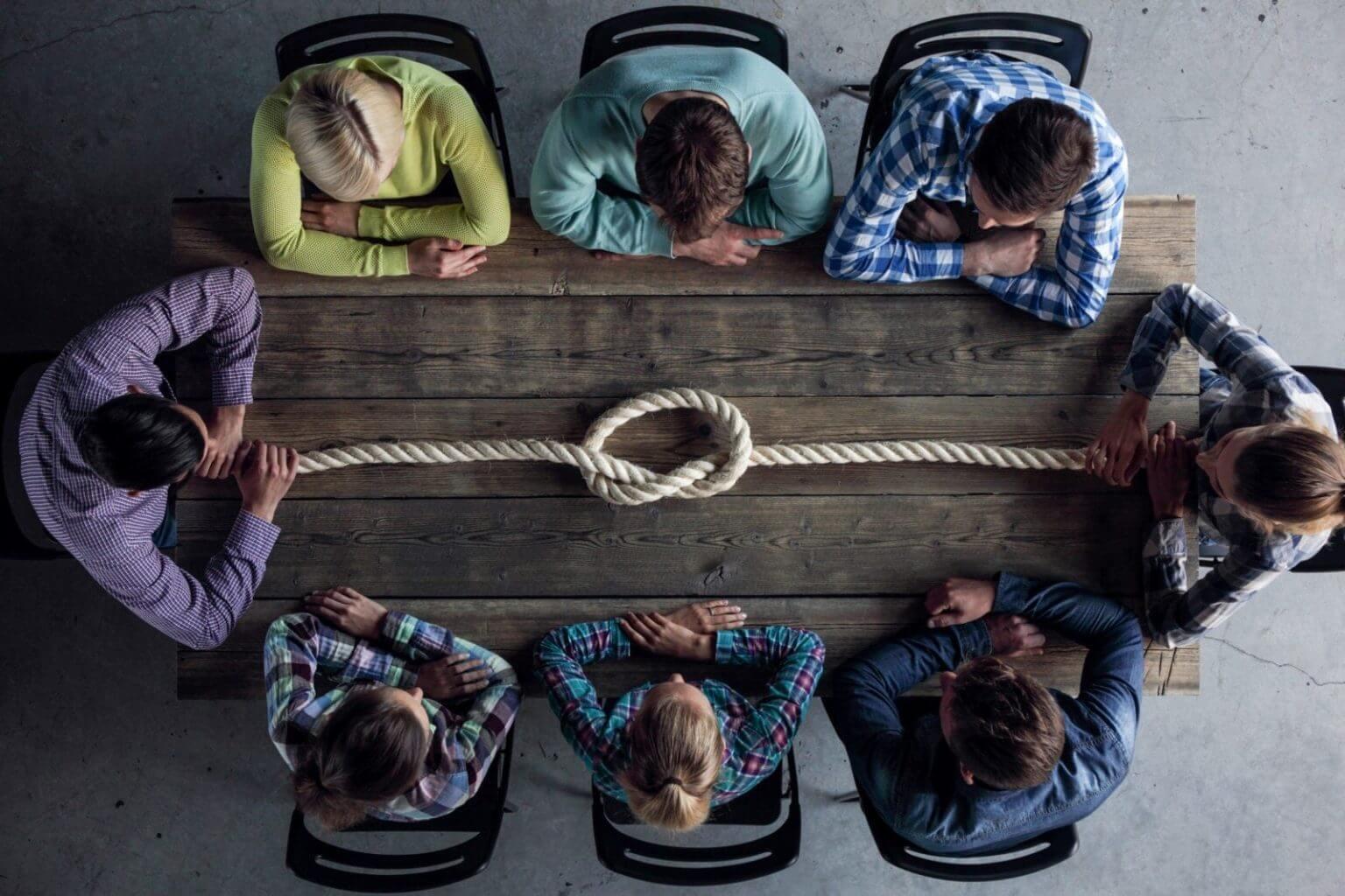 8 personer sitter ved et bord å ser på en knute. Alle har armene på bordet og sitter helt stille med blikket fremover.