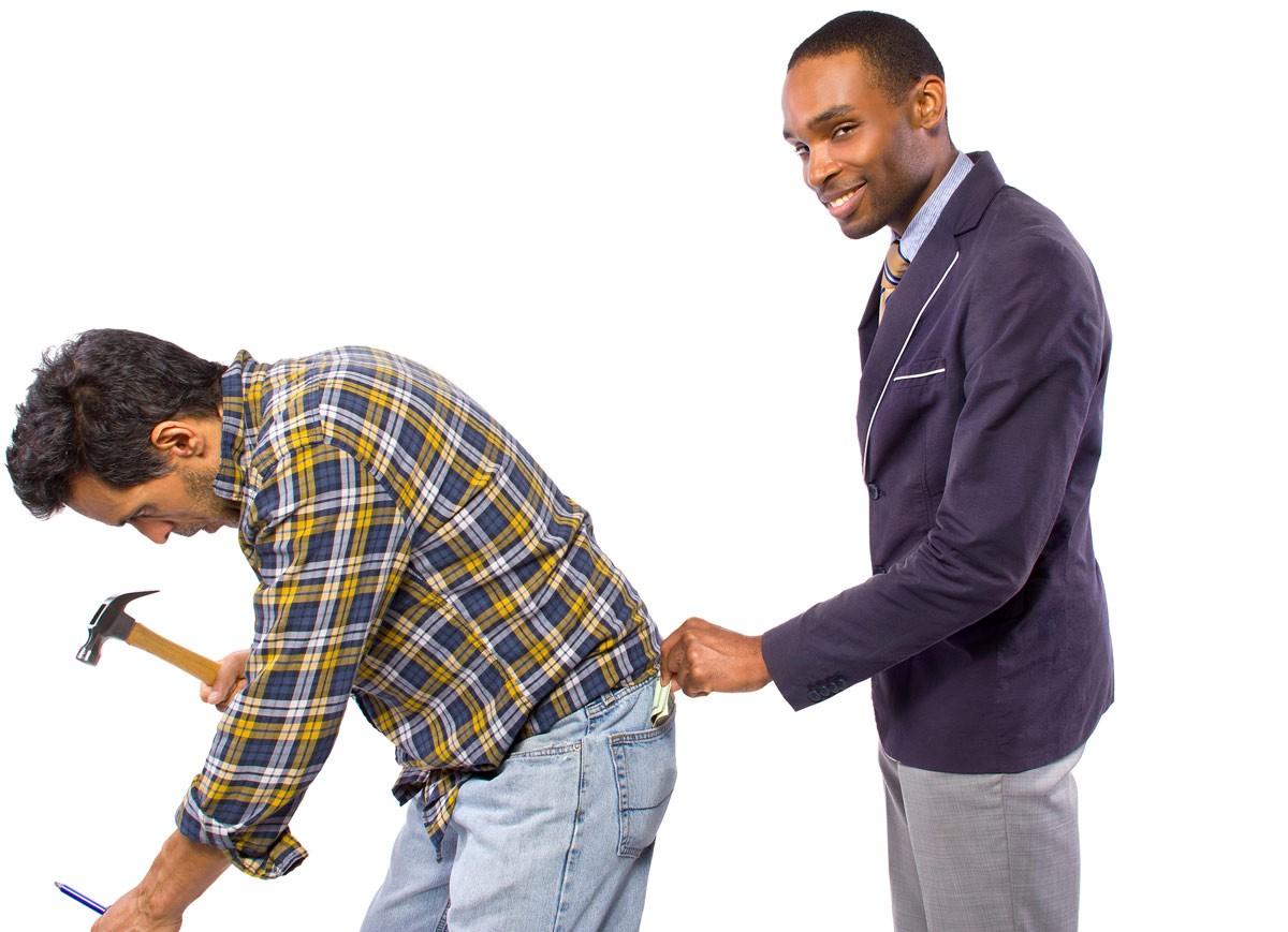En smilende mann ser inn i kameraet og tar penger fra baklomma til en annen mann som står å jobber med hammer. Mannen som jobber legger ikke merke til at pengene blir tatt.