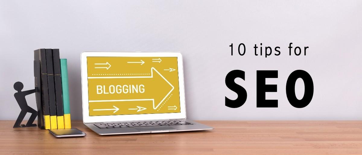 """Helt til venstre står noen bøker på en pult. LItt til høyre står en laptop med en pil der vi kan lese """"blogging"""". Pilen peker til høyre der vi ser teksten """"10 tips for SEO""""."""