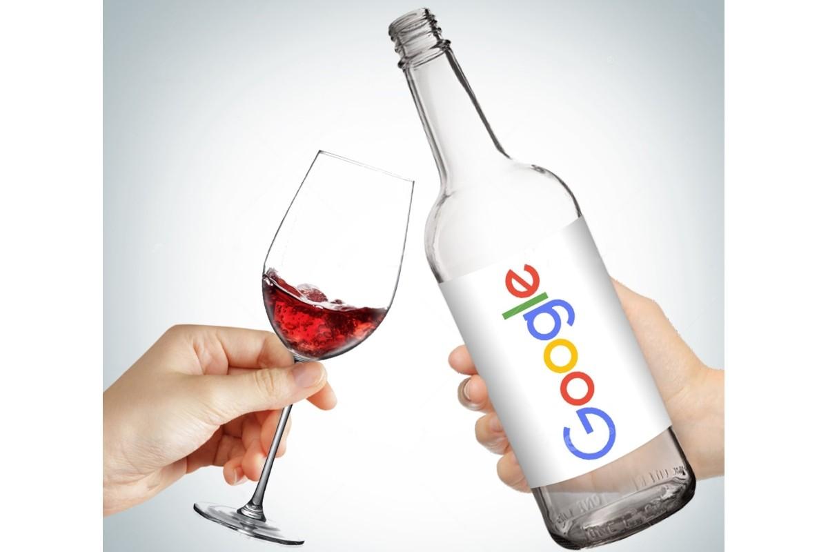 En flaske med Google-etikett skåles med et rødvinsglass.