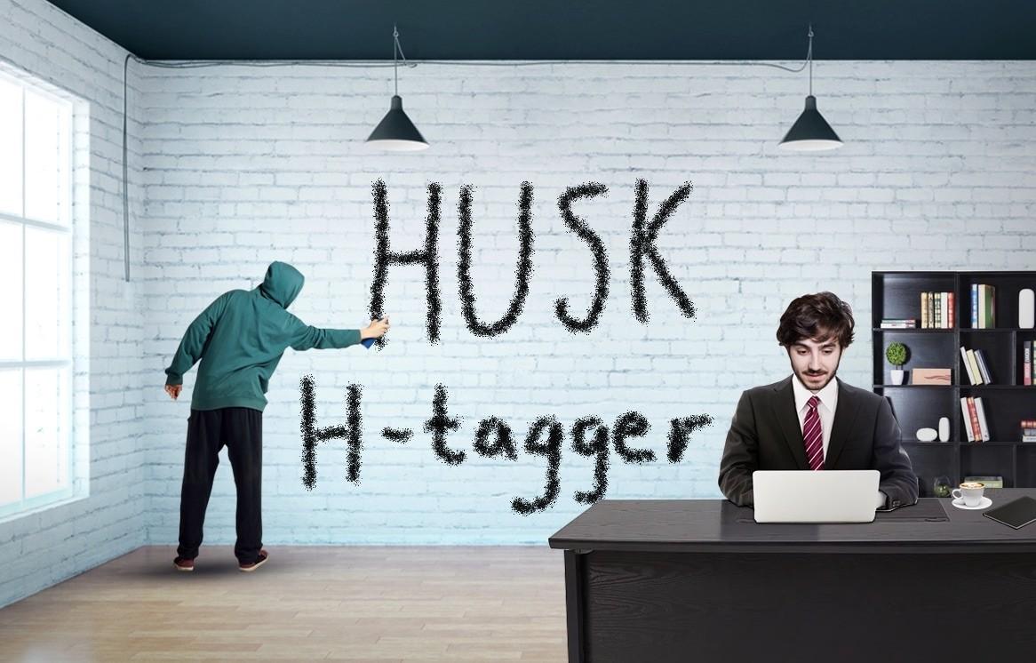 """En mann tagger på veggen der det står """"HUSK H-tagger"""". Veggen han tagger på er bakerst i et kontorlokale. I forgrunnen ser vi en mann sitte jobbende på en kontorpult."""