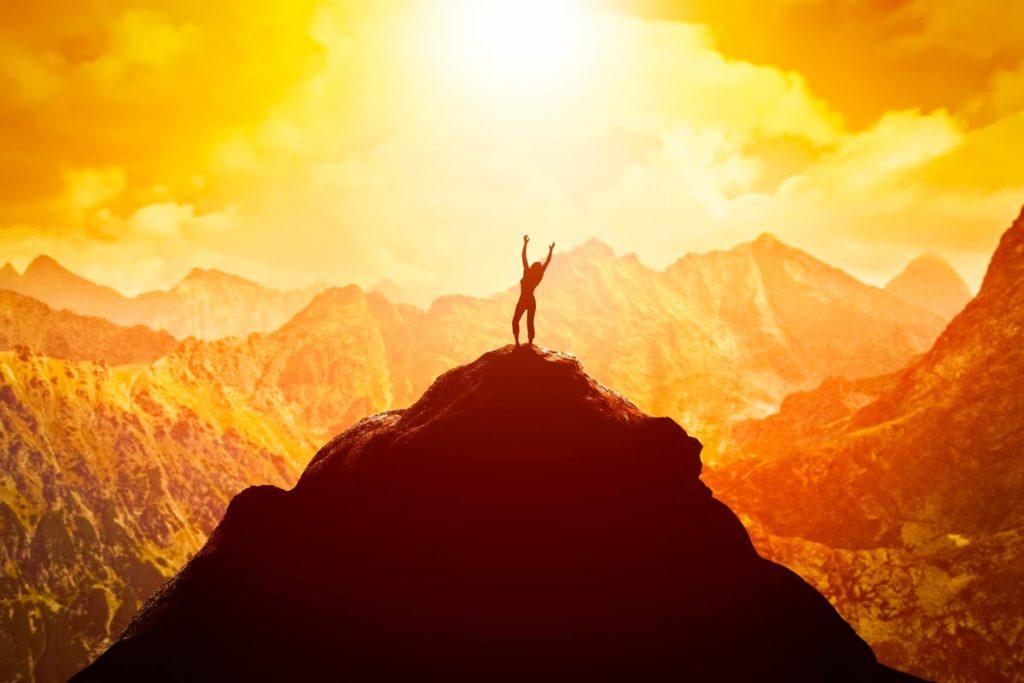 En kvinne står på toppen av et fjell med armene opp i været. I bakgrunnen er det en fjellkjede.